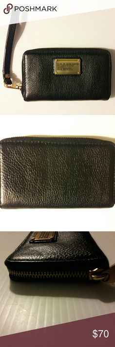 """Marc by Marc Jacobs Black Classic Q Wallet Marc by Marc Jacobs Classic Q Wingman Leather Wristlet.  A nifty leather phone wallet is accented with a rivet logo plaque and finished with a handy wrist strap.  - Wristlet strap - Zip-around closure - Interior features 2 slip pockets, 1 slip pocket, ID slot window, 4 card slots, cell phone pocket (fits iPhone 4, 4s, and 5 models) - Approx. 3.5"""" H x 6"""" W x 0.75"""" D - Approx. 6"""" wristlet strap length - ImportedMaterialsLeather exterior, textile…"""