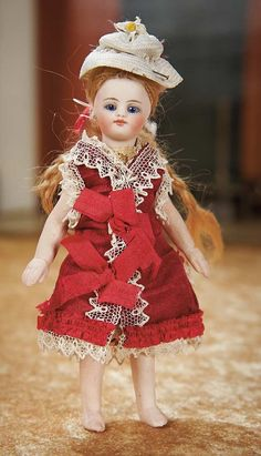 """5"""" (13cm) Solid domed bisque swivel head on kid-edged bisque torso,blonde mohair wig with hip-length braids,peg-jointed bisque limbs with bare feet. French,circa 1882,the models were shown in Parisian Etrennes catalogs,advertised as """"poupees de poche"""" (little pocket dolls). very dainty doll with delicate painting,original wig,wearing beautiful original magenta silk costume w/lace trim,undergarments,woven bonnet.  Realized Price: $1,600"""