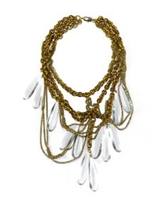 Nicole Romano Limon Necklace  Nicole Romano presents the Limon necklace, a bold and interesting piece. Multiple layers of gold chains are accented by several large, clear crystals that hang down from the chains. Other thin gold chains also mingle in with the crystals, providing for a truly eye-catching piece.