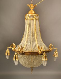 Late 19th/Early 20th Century Gilt Bronze Beaded Basket Twelve Light Chandelier.  The upper and lower part of the cage connected by ribbed bronze straps, the straps connected by bronze wreaths, six perimeter lights each held by a swan, six interior lights.Late 19th/Early 20th Century Gilt Bronze Beaded BasketTwelve Light Chandelier  The upper and lower part of the cage connected byribbed br...