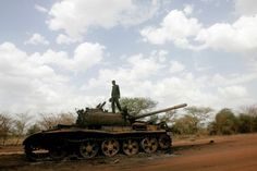 A Sudanese soldier stands atop a destroyed tank for the Sudanese Peoples Liberation Army (SPLA) of South Sudan in the oil region of Heglig on April 23. Government agencies in bankrupt Sudan have been ordered to slash their use of petrol and civil servants to donate two days of their salaries to support the army in the fight against South Sudan. (Ashraf Shazly/AFP/File)