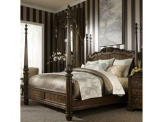 This traditional four poster bed is designed in the grand and elegant style of Western European antiques. A bed fit for royalty or just those with a taste for the finer things, the bed is hand carved with leaf and scroll trim out of walnut solids in a lush dark patina finish. The four posters are crowned with urn shaped finials, but the posts can also be replaced by reduced size posts without finials. This stately bed will draw the eye and be the decorative centerpiece of your bedroom.