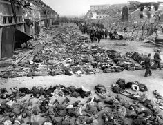 American soldiers walk by row after row of corpses lying on the ground beside barracks at the Nazi concentration camp at Nordhausen, Germany, on April 17, 1945. The camp is located about 70 miles west of Leipzig. As the camp was liberated on April 12, the U.S. Army found more than 3,000 bodies, and a handful of survivors.