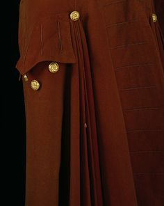 Detail, man's frockcoat, 1750-1769, Britain. The frockcoat forms part of a suit with breeches and waistcoat, all made of felted superfine russet wool. Silver-gilt buttons comprise the only adornment. Such an ensemble would have been worn as formal day wear in Britain. It was common practice to leave the side and back seams of men's coats open in the 18th century as it allowed the garment to drape comfortably while seated on a horse. Open seams also accommodated the wearing of a sword. VandA