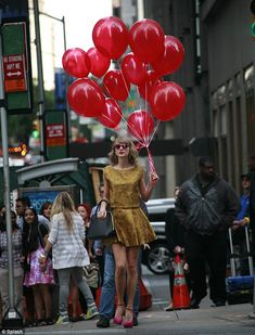 Taylor Swift was spotted carrying a dozen balloons around New York City while wearing an Alice + Olivia crop top and skirt combo and Giuseppe Zanotti pumps http://dailym.ai/1wxilGs