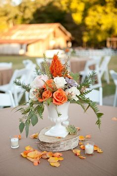 Orange and ivory roses displayed with fallen petals make a beautiful fall centerpieces. {Tiffany Hughes Photography}
