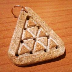 Tetraktys pitagorica (pietra levigata dal mare e smalto oro). Pythagorean yetraktys (seashore pebble and golden varnish).