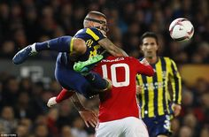 Former Liverpool defender Martin Skrtel, complete with protective face mask, takes the hands on approach to stop Rooney