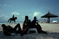 IVORY COAST. Assinie. 1978. Hotel workers, horse and tourists behind. ©Alex Webb/Magnum Photos