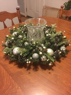 This centerpiece could easily double as a hanging wreath. Add a large candle, candle holder, or jars and dress up a dining room table or coffee table. Please note, the hurricane candle holder pictured is not included. The artificial greens and berries are wired in place. Both the