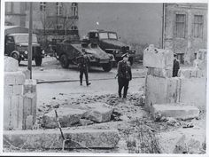 """""""GAP IN THE WALL—Communist border guards inspect a gap in the Berlin wall where two East German construction workers broke through and escaped to freedom in early April. The refugees rammed the wall with a heavy truck and then fled on foot into the French Sector of West Berlin when their truck stalled in the rubble. The East German guards fired several shots at them but missed"""