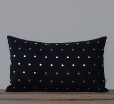 Edgy. Modern. Sophisticated. Hand-hammered gold nailheads adorn this black linen pillow cover in a sleek polka dot pattern. This gorgeous pillow