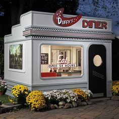 """Duffys Diner Playhouse from PoshTots $7,199.00   Usually ships within 6 Weeks* Decorated in retro-50's style, Children can sit in the miniature booth to order or visit the drive-up window. The Diner even has an operable skylight. Burgers and shakes have never tasted so good. Base Size: 8' wide x 6' deep.Bottom of base to peak: 88"""", Door height: 56""""; width: 24"""", Wall Height: 60"""""""