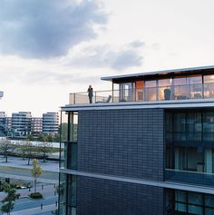 Cox enjoys the view from his penthouse terrace. The steel used for the terrace, and the brick-colored cladding of the building, echo the industrial architecture of the area. The angles suggest a ship, a nautical link with Duisburg's past as a major port. German Architecture, Industrial Architecture, Architecture Design, Penthouse Apartment, Apartment Complexes, Brick Colors, Brick Building, Cladding, Skyscraper