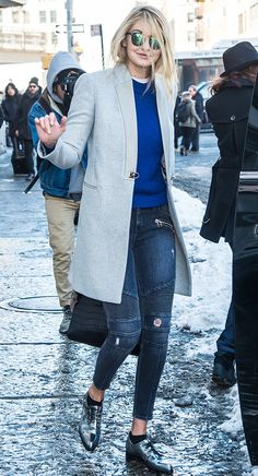 Gigi Hadid wearing a long grey coat, cobalt crew neck sweater, cropped skinny jeans with textured striped along the knees and distressed areas throughout, and metallic pointed-toe shoes