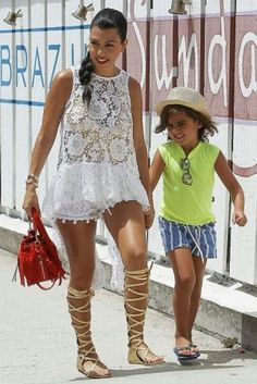 Kourtney Kardashian wearing Chanel Resort 2011 Gold Gladiator Sandals and Saint Laurent Emmanuelle Fringe Bucket Bag