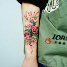 Beautiful floral bouquet tattoo on forearm by Nando