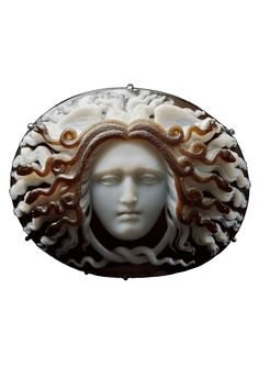 An antique Medusa cameo by Benedetto Pistrucci, circa 1844. Layered agate cameo head of the Medusa facing front, eyes cast downwards, mouth pursed in a bitter expression, hair standing out stiffly parallel with the wings at the top of the head. The oval face is framed within five pairs of snakes coiled into spirals terminating in heads hissing outwards amidst the locks of heir: two tails are knotted beneath the chin. Signed PISTRUCCI, for Benedetto Pistrucci.