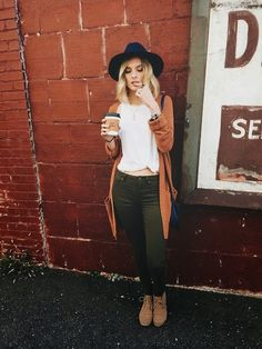 Black wide brim hat + burnt orange cardigan + white top + olive green pants + short grey boots