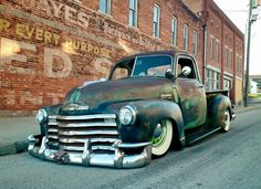 1947-1951 Chevy Advanced Design pickup truck in a cool green patina finish and sporting what looks like a 50s Caddy or maybe Lincoln front bumper and then dumped on the ground over artillery wheels and wide white wall tires.