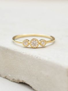 This ring is a gorgeous compliment to our other stacking rings. The ring features three stones set on a very thin round band. All three stones are very small. This ring looks great on its own for a cl