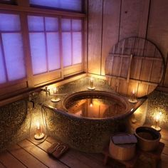 Rustic wood and stone bathroom with a round hot tub, lighted by candles