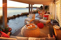 A breezy patio expansion preserves the views of the Puget Sound while providing covered seating to enjoy the scenery. A round woven seagrass coffee table, versatile outdoor rugs and red accents keep the look decidedly relaxed and coastal.