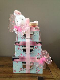 Kraamcadeau van doosjes met daarin slaapzakje, flesje, sokjes, slabbertjes, badschuim, haarlotion, knuffel en tandendoosje. Versierd met lint en vlinders.