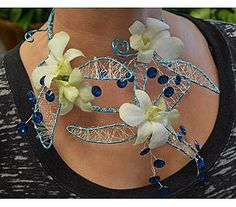 Artistically hand crafted Prom necklace is created with 12 gauge blue wire, 28 gauge silver crimped wire, faux blue rhinestones and white dendrobium orchids