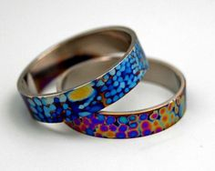 Titanium rings anodized using a brush that had electricity running through it.