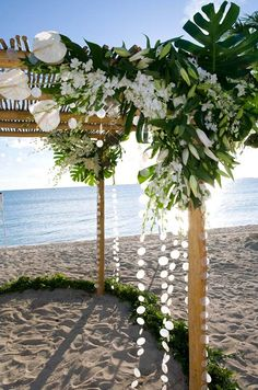 An arbor features anthurium, monstera leaves, orchids and beautiful lilies that have yet to fully bloom.