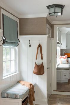 Brown and blue mudroom features top part of walls clad in brown grasscloth and bottom part of walls clad in white shiplap lined with hooks.