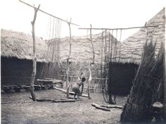 """Nigeria, Yoruba adult [male or female?] """"stretching dyed cotton yarn"""" for """"drying"""" over large wooden framed made from tree-trunks and poles. Section-view of child [male?] and bundles of grass at right. Settlement setting, single-storey thatched-roof buildings in background. Medium: Gelatin silver print."""