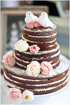 "A naked cake decorated with powdered sugar and roses: an inexpensive wedding cake you can DIY. Still looks elegant and and chic with a lot less headache! - the bottom layer seems large, so maybe just the top two layers if you don't have pans that large - depending on the number of guests, you would have other I decorated cakes cut up and ready to serve to go along with the ""display cake."""