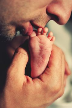 Father kissing baby toes