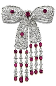 AN IMPORTANT RUBY AND DIAMOND DEVANT DE CORSAGE, EARLY 20TH CENTURY.  Designed as an open work tied ribbon bow, millegrain-set with circular- and single-cut diamonds accented with mixed-cut rubies, the articulated bow suspending a ruby and diamond fringe of bell flower design, one diamond deficient, detachable brooch pin to reverse.