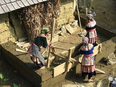 Woman build an extension to a home in North Vietnam. In this technique, strips of wall are built horizontally, 2 wooden panels are held together with wooden clamps and keys or rope. Once one portion of a wall is completed, the formwork is immediately dismantled and moved further along the wall. Every course is rammed till the soil gives a clear sharp sound and the rammer is not making anymore marks on the layer.