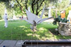Pájaros de papel colgados de los árboles del jardín.