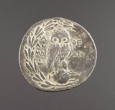 A silver coin from ancient Athens featuring an owl (symbol of the goddess Athena), an olive branch and an amphora for olive oil, symbols of Athens, Greece. (The J Paul Getty Museum)