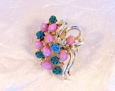 So pretty and feminine brooch or pin by Coro. The brooch features carved lucite flowers - turquoise ones that look like roses and pink ones that look like rose buds. Reminds me a spring or summer. It is accented with three bright clear rhinestones to add just a little sparkle. All in a silver tone. The brooch measures approximately 2 1/4 the long way and 1 3/4 the short way. The brooch is signed Coro on the back, but not deeply struck so difficult to see. I took the best picture I ...