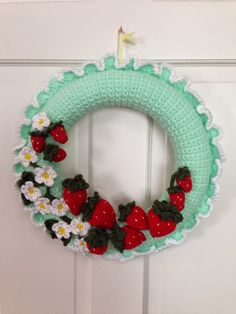 Strawberry Wreath with strawberry blossoms with ruffles around wreath - Katie's idea based on a her Strawberries and Cream dress. Made from various patterns : Strawberry Pattern is from http://happyberrycrochet.blogspot.com/2013/11/how-to-crochet-strawberry.html Flower is Apple Blossom from 100 Flowers to Knit & Crochet Leaves from  Leaves 101 http://cre8tioncrochet.com/2013/01/free-crochet-sprin-pattern-leaves-101/ Wreath is standard crocheted wreath cover & ruffle my own design.