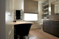 source: Carden Cunietti  Contemporary bedroom with claw foot tub, hardwood floors, coffee stained bathroom vanity and stainless steel towel warmer.