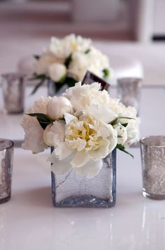 White orchids and bud vases full of of ranunculus cover the center of a table with crystals and dendrobium orchids hanging above.