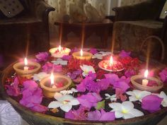 floating flower heads and candles in a shallow bowl