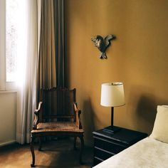 An antique chair sits comfortably in the corner of a mustard-walled bedroom | Block Print Social