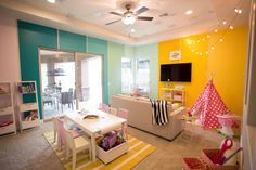 Gradient+color+on+two+accent+walls+gives+punch+to+this+creative+playroom.+A+rug+and+kid-size+work+table+define+an+area+for+crafts+and+playtime,+while+a+small+sofa+offers+a+family-friendly+spot+for+TV+watching.