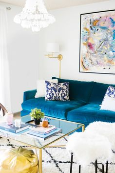 Tour A Small Apartment Brimming with Chic DIY Style // gold pouf, blue velvet couch, ikat pillow, glass coffee table, diamond rug