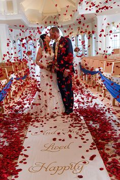 Kisses in a confetti of red rose petals at Disney's Wedding Pavilion