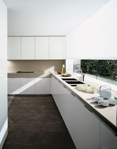 Matte white slab doors come to life with the texture and contrast from the dark flooring