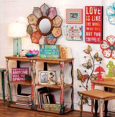 déco de style hippie chic - table d'appoint en bois ornementé, miroir rond avec cadre décoratif à motifs colorés et papillons et fleurs accrochés au mur comme accent
